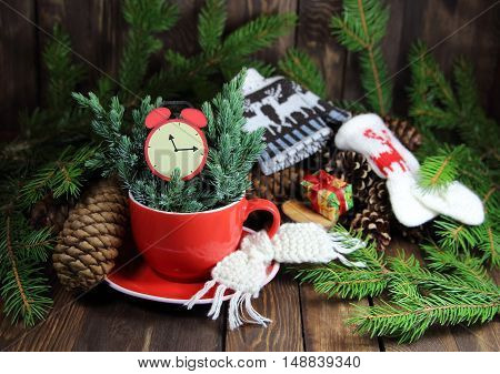 cup red with a knitted scarf, a fir-tree, cones and a red alarm clock