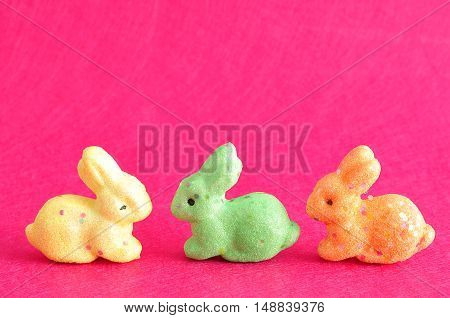 A row of colorful bunnies used for decoration over the easter period isolated on a pink background