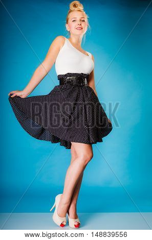 Retro pin up woman style. Beauty young full length girl on blue background in studio.
