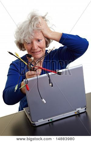 Senior Woman With Laptop And Many Cables