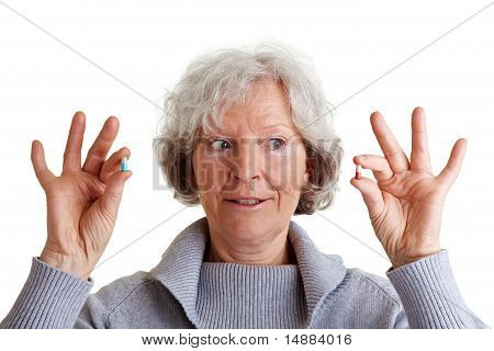 Senior Woman Comparing Two Pills