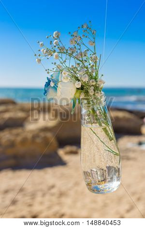 detail from wedding of bouquet in mason jar. On the background of the ocean.