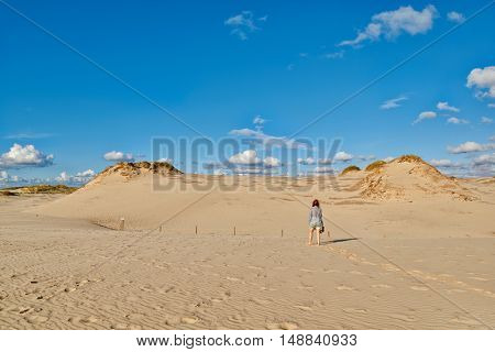 Young redhead woman walking under sun along endless sandy dunes of Leba, Poland