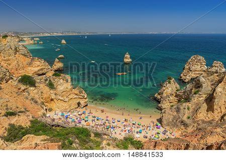 Camilo Beach, Lagos in the Algarve. Tourists sunbathe on the sand.