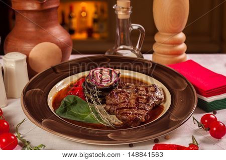 Steak With Onions And Basil In A Restaurant On A Plate