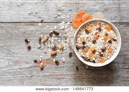 bowl of muesli with dry fruits and nuts on rustic wooden background. top view