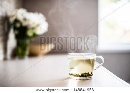 Cup of fresh green tea with steam on a morning table