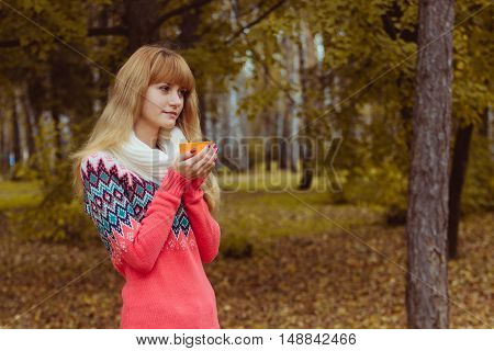 Fall concept - autumn woman drinking coffee in park. Beautiful young modern woman smiling happy and cheerful