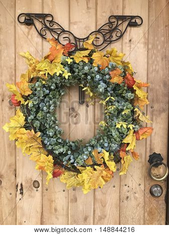 A fall wreath on a wooden door background.