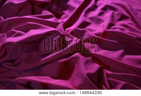 Elite bedclothes. Red wrinkled fabric texture background