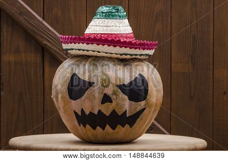 Halloween pumpkin with mexican hat on wooden background