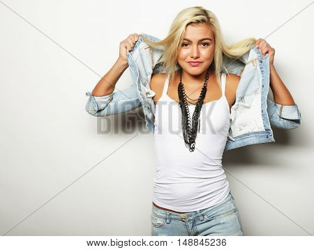 Close up studio portrait of cheerful blonde hipster girl going crazy making funny face