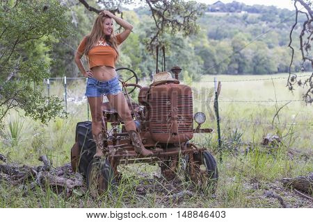 Brunette model with an old tractor