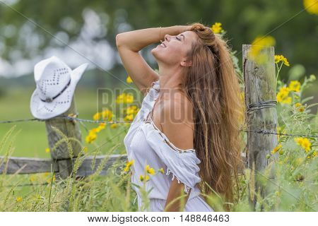 Brunette model relaxing in a field of flowers