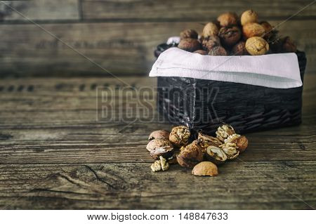 Fresh walnuts in a basket on autumn background on the old wooden table, healthy eating cocept. Selective focus