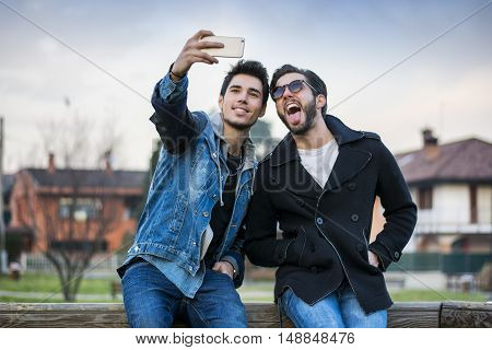 Two young men taking selfie while sitting on bench outdoors