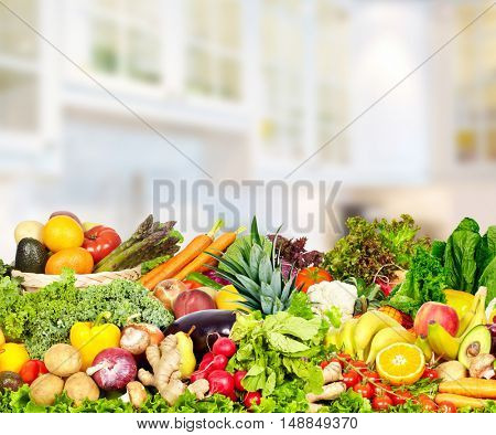 Vegetables and fruits over kitchen background.