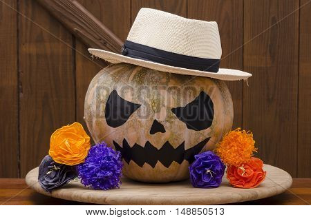 Halloween pumpkin on wooden background with colorful flowers. Gangster