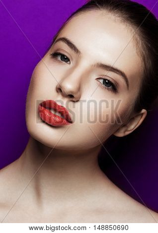 Beautiful woman with makeup red lips on purple background. Open neck