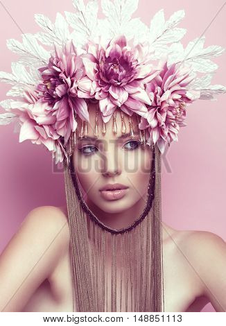 Beautiful woman with flower crown and makeup on pink background. Crown with chain below