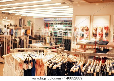 Clothes on hangers in a clothing store. Selective focus on the foreground blurred store interior on background. Warm toned image