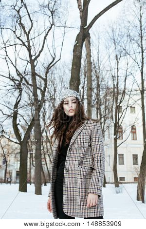 young pretty stylish modern hipster girl outside on street, fashion coat, hairstyle, make up, lifestyle people concept close up citylife, winter coming