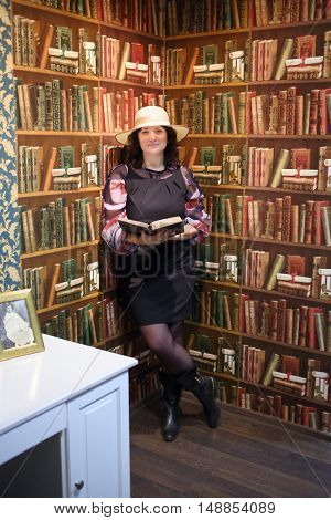 MOSCOW - MAR 17, 2015: Blogger in a black dress and a white hat with an open book stands near a wall with painted shelves and books in the quest Funlock for bloggers