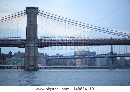 NEW YORK, USA - SEP 07, 2014: Brooklyn Bridge in front of Manhattan Bridge crossing the East River in the evening