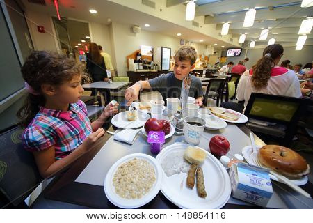NEW YORK, USA - SEP 08, 2014: Boy and girl (with model release) eating breakfast at a table in a restaurant