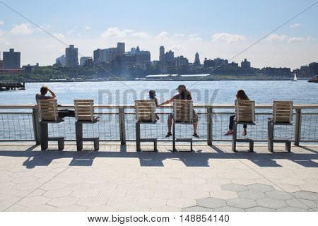 NEW YORK, USA - SEP 07, 2014: People sit on chairs and admire the views of the Brooklyn side of Manhattan