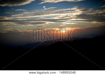 sunset background, mountain silhouette foreground, beautiful sky