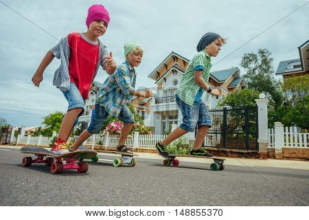 Little boys on longboard skates on the road