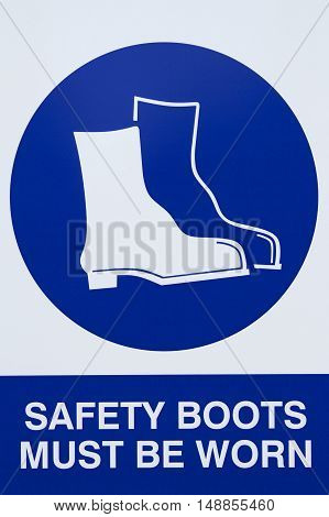 Safety boots signage at a construction site.