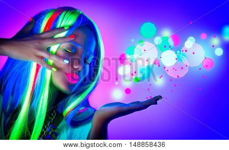 Fashion model woman in neon light, beautiful model girl, painted fluorescent make-up, Body Art design of female disco dancer blowing neon sparks in UV, colorful make up. Gestures for advertisement