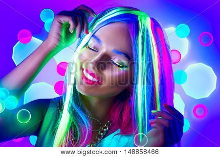 Fashion model woman dancing in neon light, portrait of beautiful model girl with fluorescent make-up, Body Art design. Disco dancer posing in UV, painted face, colorful make up, on colorful background