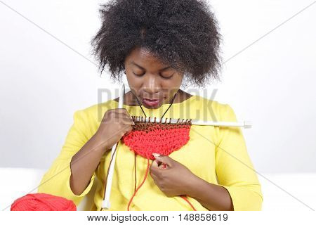 African Woman Knitting, Sitting On A White Couch.