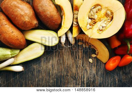 Autumn vegetables on wooden b background, top view