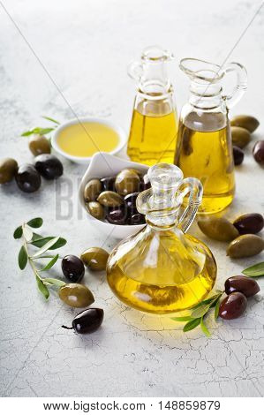Olive oil in vintage bottles with black and green olives and leaves on white background