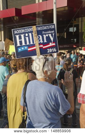 Asheville, North Carolina, USA: September 12, 2016: Senior Woman holds a Hillary Clinton sign at a Donald Trump campaign rally among a throng of protesters on September 12, 2016 in downtown Asheville, NC