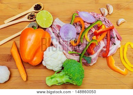 raw pork in marinade, on a cutting board with tomatoes on a branch, a knife for meat and seasonings border , place for text on wooden rustic background top view