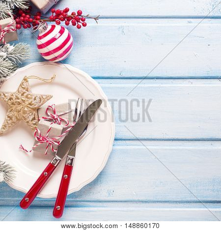 Christmas table setting. White plate knife and fork napkin and christmas decorations in white and red colors on blue wooden table. Top view. Selective focus. Toned image.