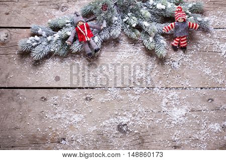 Christmas elfs and branches fur tree on aged wooden background. Decorative christmas composition. Selective focus. Place for text.