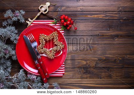 Empty plate knife and fork napkin and christmas decorations on dark wooden table. Christmas table setting. Selective focus. Place for text.
