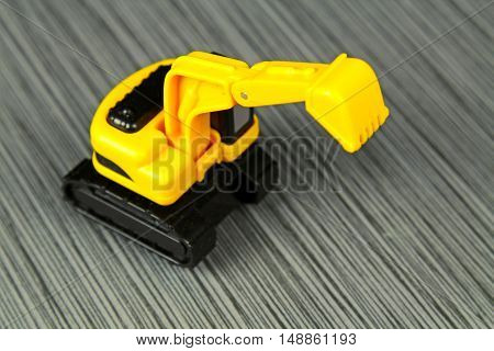 A yellow toy truck on a grey stone background with copy space selective focus