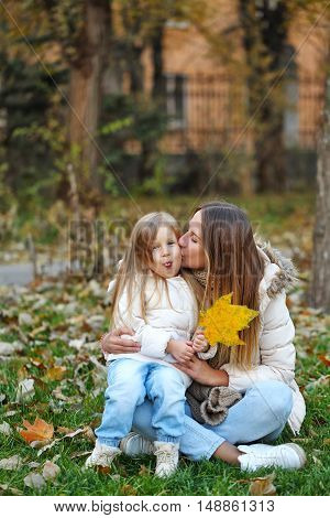 Family walk. Mother kissing daughter. Baby shows tongue. Fallen leaves. Autumn Park. Cute family relationships.