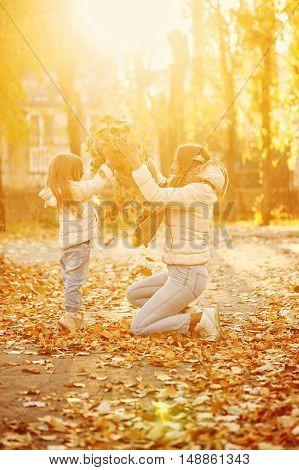 Family walk. Mother and daughter throw up leaf litter. Autumn Park. Cute family relationships. Sunset. Warm toning.