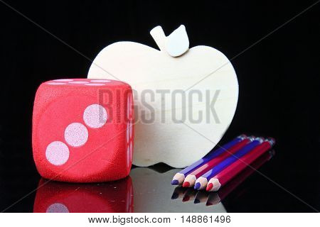 Blue and red pencils with an apple cutout on a black background for the back to school theme with copy space.