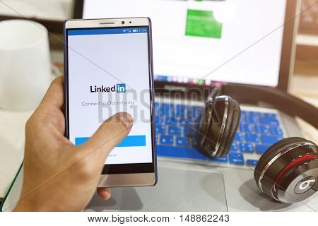Man Hand Holding  Android Device With Linkedin On The Screen