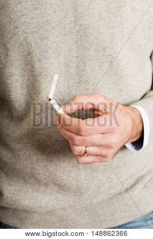 Male hand with broken cigarette