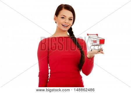 Smiling young woman holding small empty shopping cart